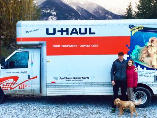 Tillman Scholar, woman and dog outside of U-Haul truck in snowy forest.
